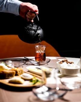 Мужчина наливает черный чай в армуди национальный стеклянный вид сбоку