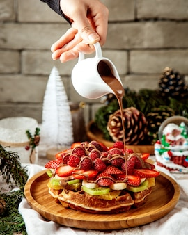 Man pouring chocolate on waffle with fruit slices
