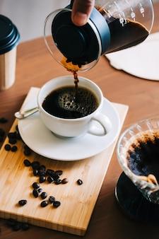 カップにコーヒーを注ぐ男性、代替のコーヒー醸造方法、ドリッパーとペーパーフィルターの上に注ぐことを使用します。