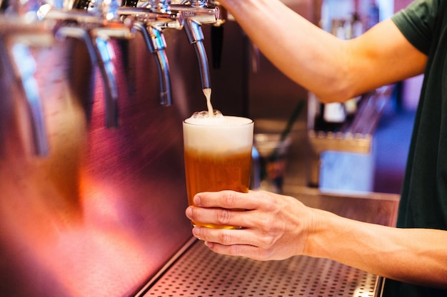 Man pouring craft beer from beer taps in frozen glass with froth.