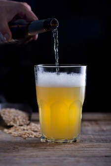 Man pouring craft beer into glass, dark wooden table