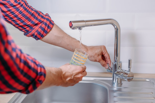 Man pouring glass of water from tap with clean filter in kitchen, close up