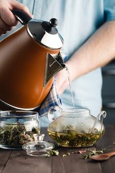 Мужчина наливает травяной чай в стакан