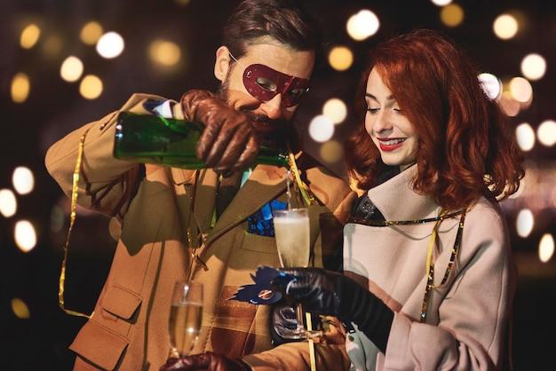 Мужчина наливает жене бокал шампанского с шампанским