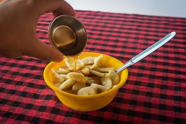 바나나와 꿀 오트밀을 붓는 남자. 건강한 아침 식사