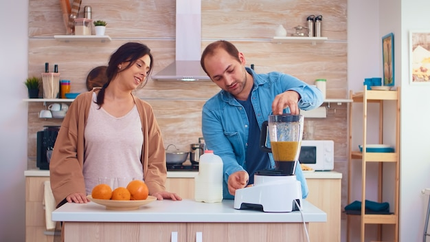 Мужчина наливает молоко в блендер для свежего и здорового смузи для него и веселой жены. веселая семья вместе готовит органический здоровый свежий питательный вкусный сок на завтрак из свежих фруктов, пока