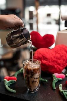 Мужчина наливает молоко в стакан кофе со льдом с красными сердечками
