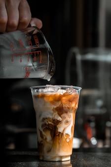 Мужчина наливает молоко в стакан кофе со льдом