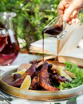 Man pouring nar-sharab pomegranate sauce on the grilled chicken served with lemon