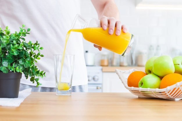 Man pouring orange juice from jug into glass in the kitchen is in sunlight.
