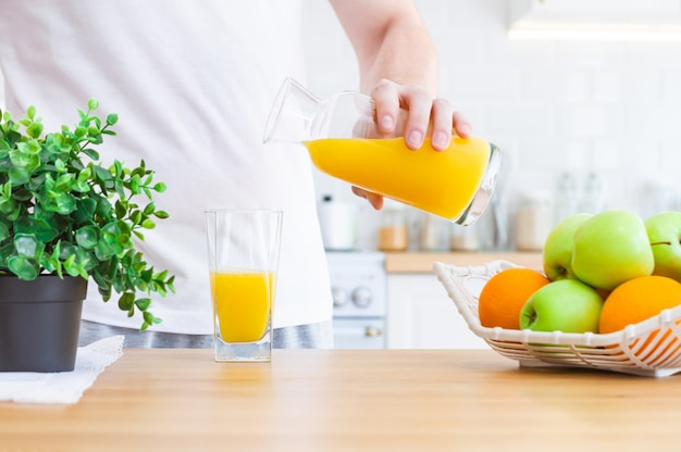 Man pouring orange juice from jug into glass in the kitchen.