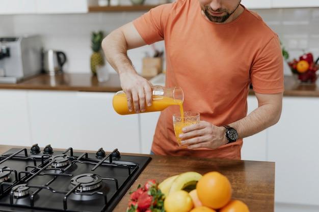 ガラスにオレンジジュースを注ぐ男
