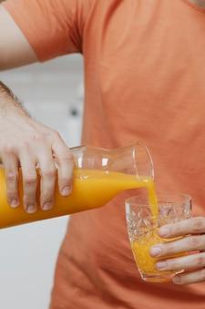 グラスにオレンジジュースを注ぐ男