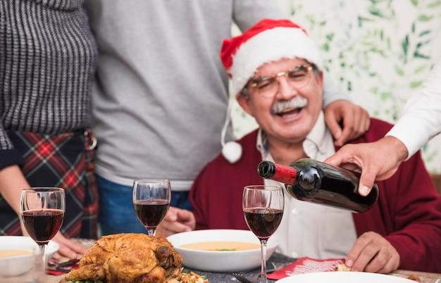 축제 테이블에 유리에 레드 와인을 붓는 사람