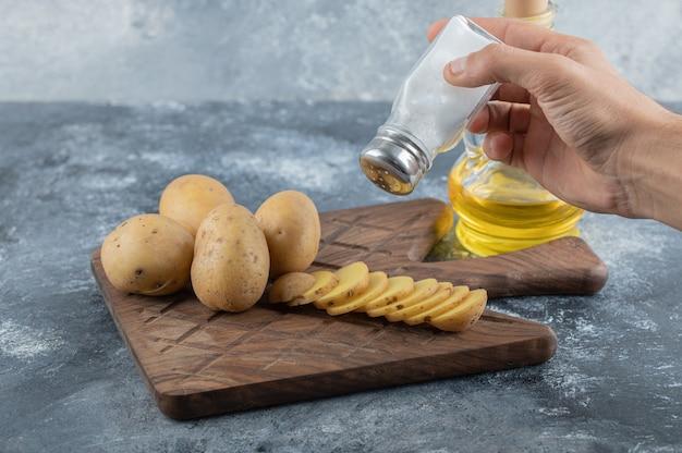 スライスしたジャガイモに塩を注ぐ男。高品質の写真