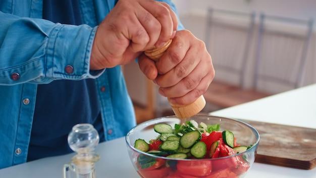 おいしい食事のためにキッチンでヘルシーなサラダに塩を注ぐ男。健康的な有機食品を一緒に幸せなライフスタイルを準備する料理。野菜と家族での陽気な食事