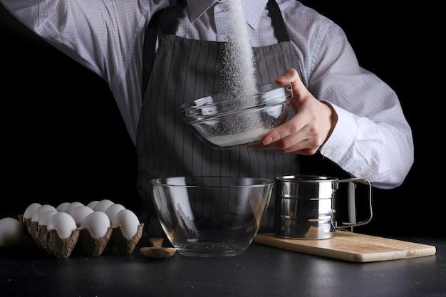 Человек наливает сахар в миску на черном фоне