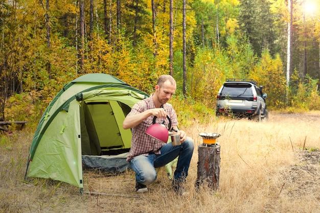 秋の森の彼の緑の観光テントの近くのやかんからお茶を注ぐ男