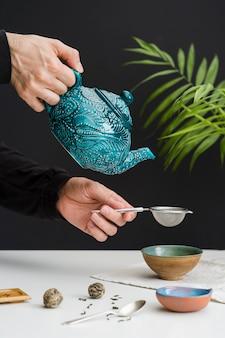 ストレーナーを通してボウルにお茶を注ぐ男