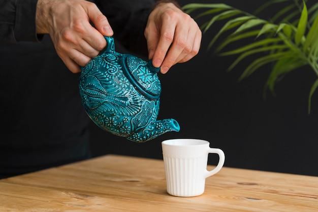マグカップでお茶を注ぐ男