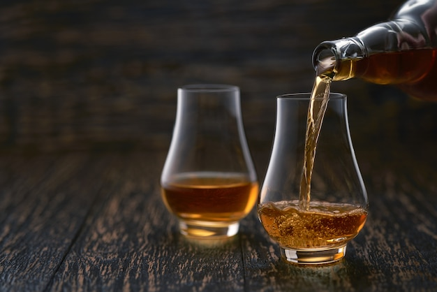 Man pouring whiskey in glasses  on rustic wooden table selective focus.