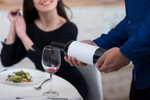 彼の妻のためにグラスにワインを注ぐ男