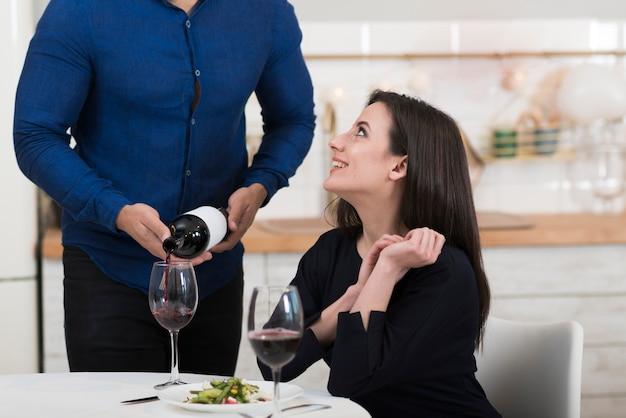 Мужчина наливает вино в бокал для своей жены
