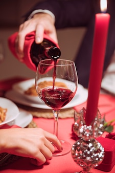 Man pouring wine in glass on festive table
