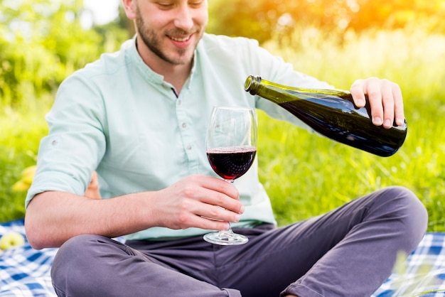 Man pouring wine into glass on picnic