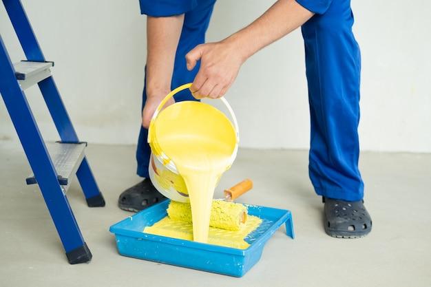 Человек наливает желтую краску в лоток.