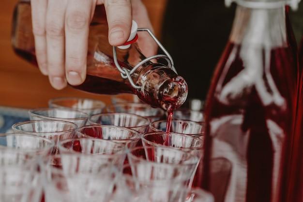 男はグラスに赤い飲み物を注ぐ