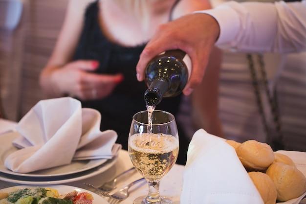 Мужчина наливает шампанское из бутылки в стакан