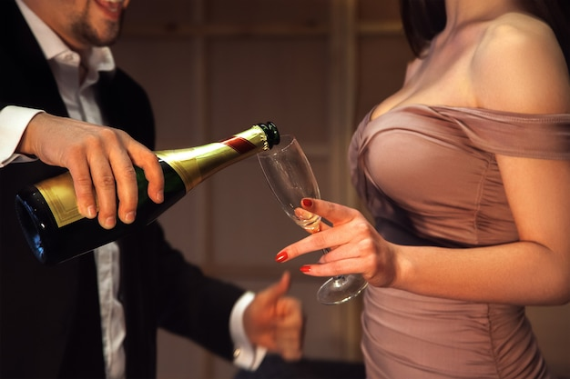 男はガールフレンドのためにグラスにシャンパンを注ぐ。休日とお祝いの概念