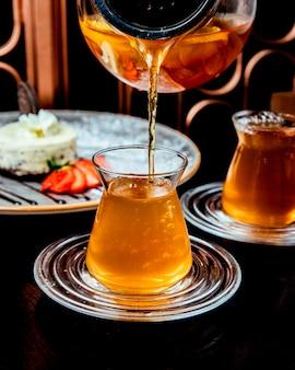 L'uomo versa il tè di agrumi nella vista laterale di vetro