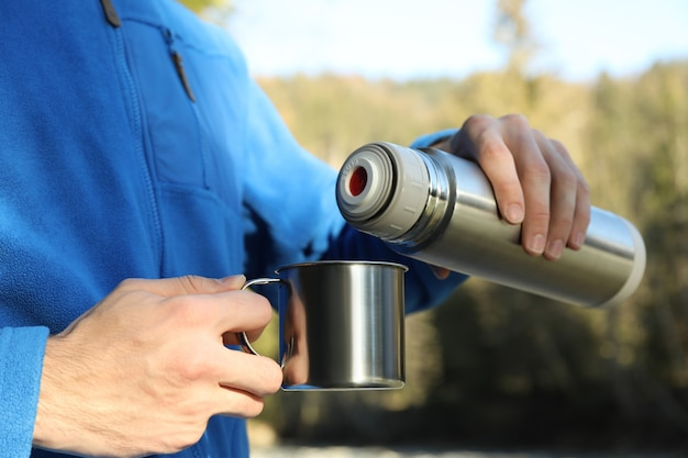 A man pours coffee from a thermos into a cup in forest