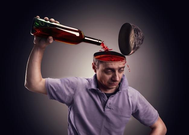 Мужчина поливает голову спиртом над серым