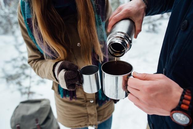Человек наливает горячий чай из термос в кружку. крупный план
