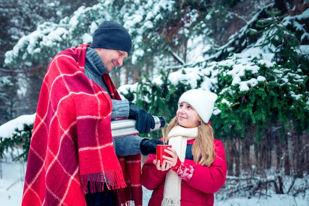 Man pours hot tea out of thermos for his daughter