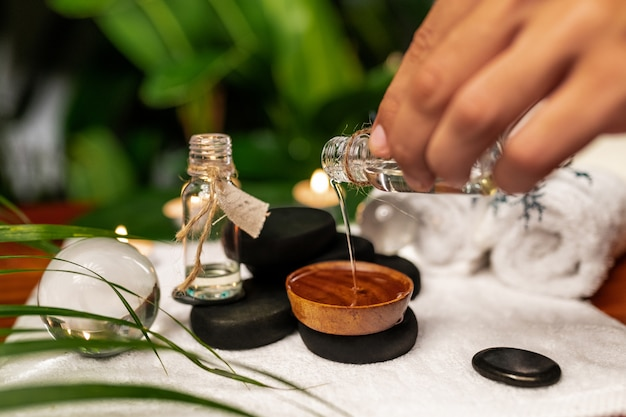 A man pours oil from a jar of essential oils standing on stones for a therapy stone and located on a terry towel next to which are transparent spheres