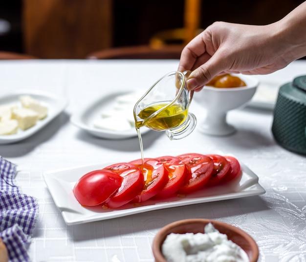 남자는 얇게 썬된 토마토 측면보기에 올리브 오일을 부 어