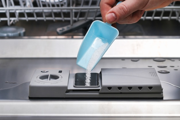 A man pours powder for washing dishes into the dishwasher compartment.