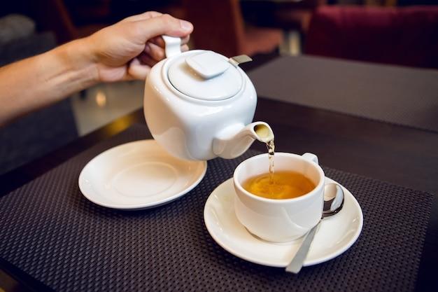 Мужчина наливает чай из белого чайника в чайную чашку, блюдце и чайную ложку, сахарницу стоят на столе