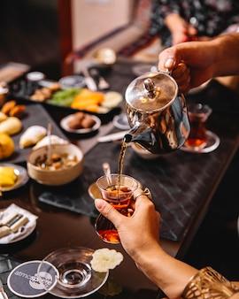 Man pours tea from tea pot into armudu glass served for tea setup