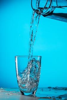 男はスタジオでガラスから青い背景のガラスに水を注ぐ
