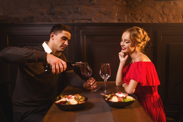 男はグラスにワインを注ぐ、レストランで若い愛のカップル、ロマンチックなデート。赤いドレスを着たエレガントな女性と彼女の男、記念日のお祝い