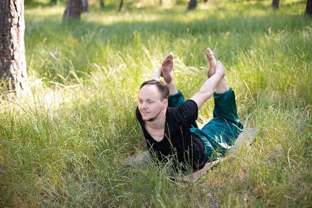 男は背の高い草の中で自然の中でヨガを練習します