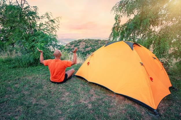 Мужчина занимается йогой возле оранжевой палатки на холме