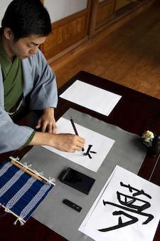 さまざまなツールで日本語の手書きを練習する男