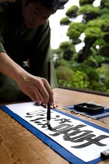 Uomo che pratica la scrittura giapponese con un assortimento di strumenti
