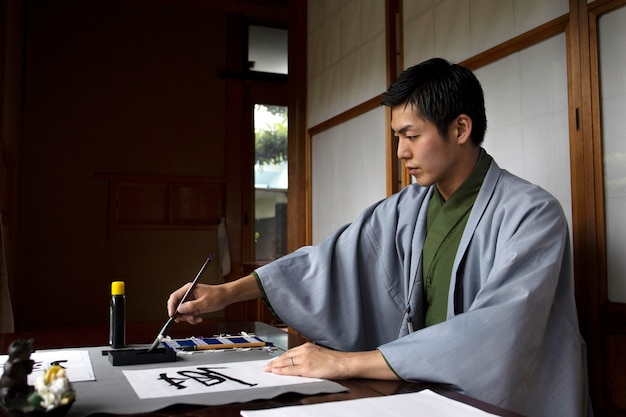 Uomo che pratica la scrittura giapponese con un pennello